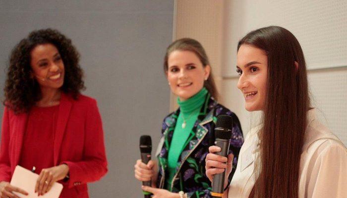 Bühnenmoderatorin Anne Chebu im Gespräch mit zwei Jugendlichen